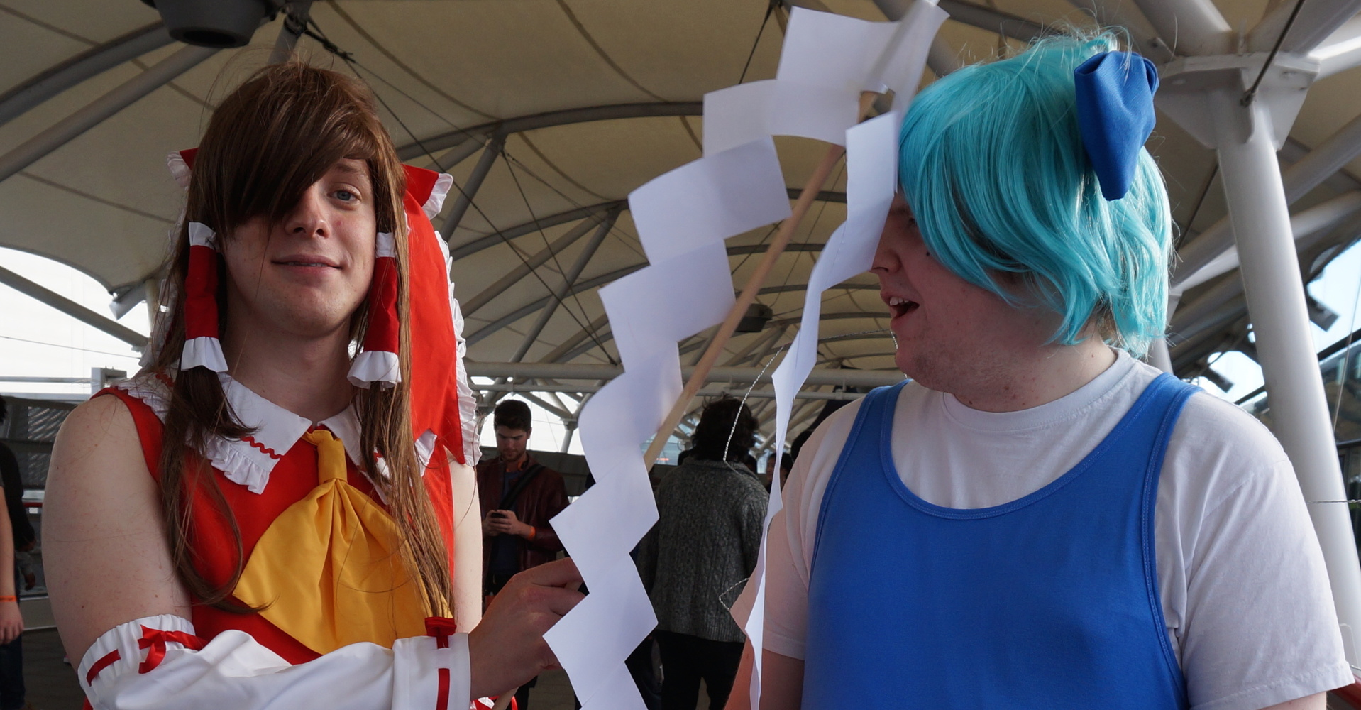 Two white dudes dressed as Touhou characters. The one on the left (Reimu, in a frilly red dress and long brown wig) is hitting the one on the right (Cirno, wearing a short blue wig, a blue dress, and wire fairy wings) with a home-made gohei.